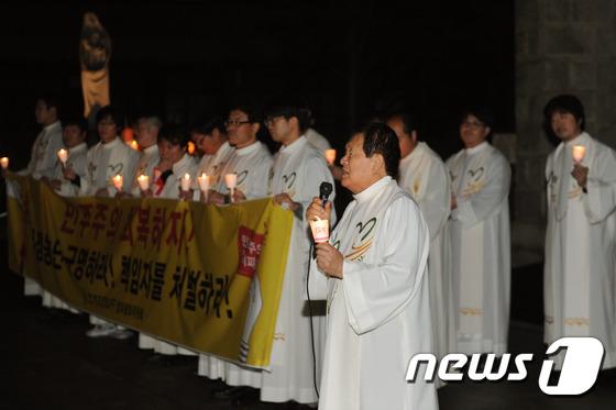 십자가든 사제들 촛불까지 들었다