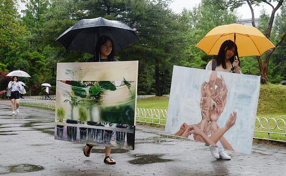 '그림이 비에 젖지 않도록 조심 또 조심'