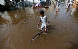 물이 가득한 거리에서 자전거 타는 소년