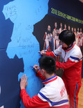 한반도 지도에 사인하는 북한 탁구선수들