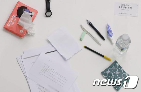 논술 시험 \'시계, 필기도구, 물 놓인 책상\'